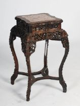 A Chinese dark wood urn stand, Qing Dynasty, the shaped square top with a mottled red and white