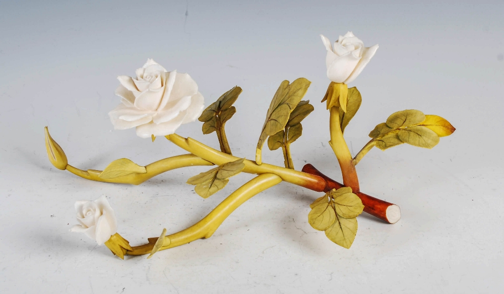 A Chinese ivory and stained ivory rose branch, late 19th/ early 20th century, naturalistic carving