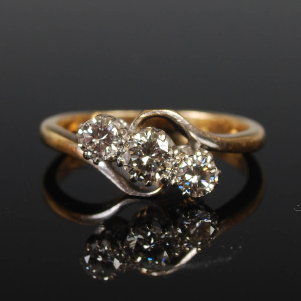 A yellow and white metal three stone diamond ring, mid 20th century, set with a single round