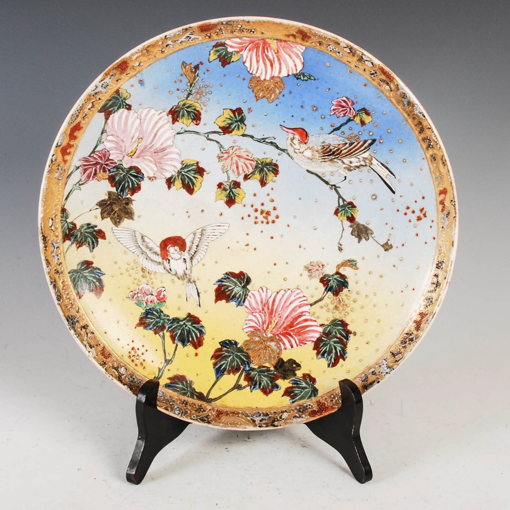 A Japanese Satsuma pottery charger, Meiji Period, decorated in coloured enamels with pair of