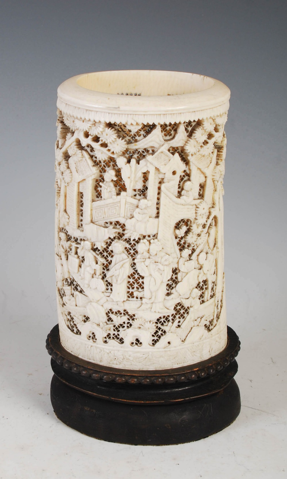 A Chinese ivory tusk vase, Qing Dynasty, carved with figures, pavilions and pine trees on a