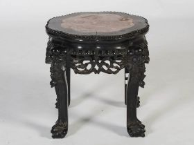 A Chinese dark wood jardiniere stand, Qing Dynasty, the shaped octagonal top with mottled red and