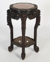 A Chinese dark wood jardiniere stand, Qing Dynasty, the shaped octagonal top with a mottled red