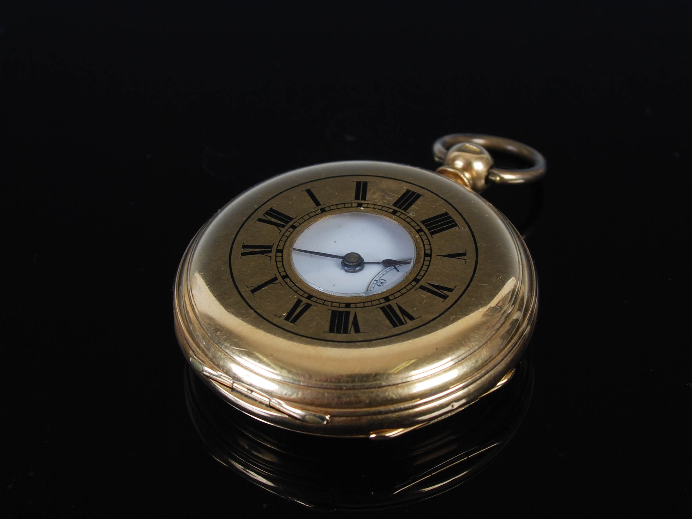 A yellow metal half hunter pocket watch, the outer cover with black enamel Roman numeral detail, the