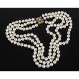 A cultured pearl necklet with 9ct gold and pearl set clasp, triple matinee length rows of forty-