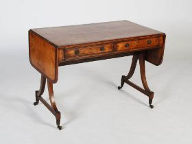 An early 19th century mahogany and rosewood sofa table, the rectangular top with twin drop leaves