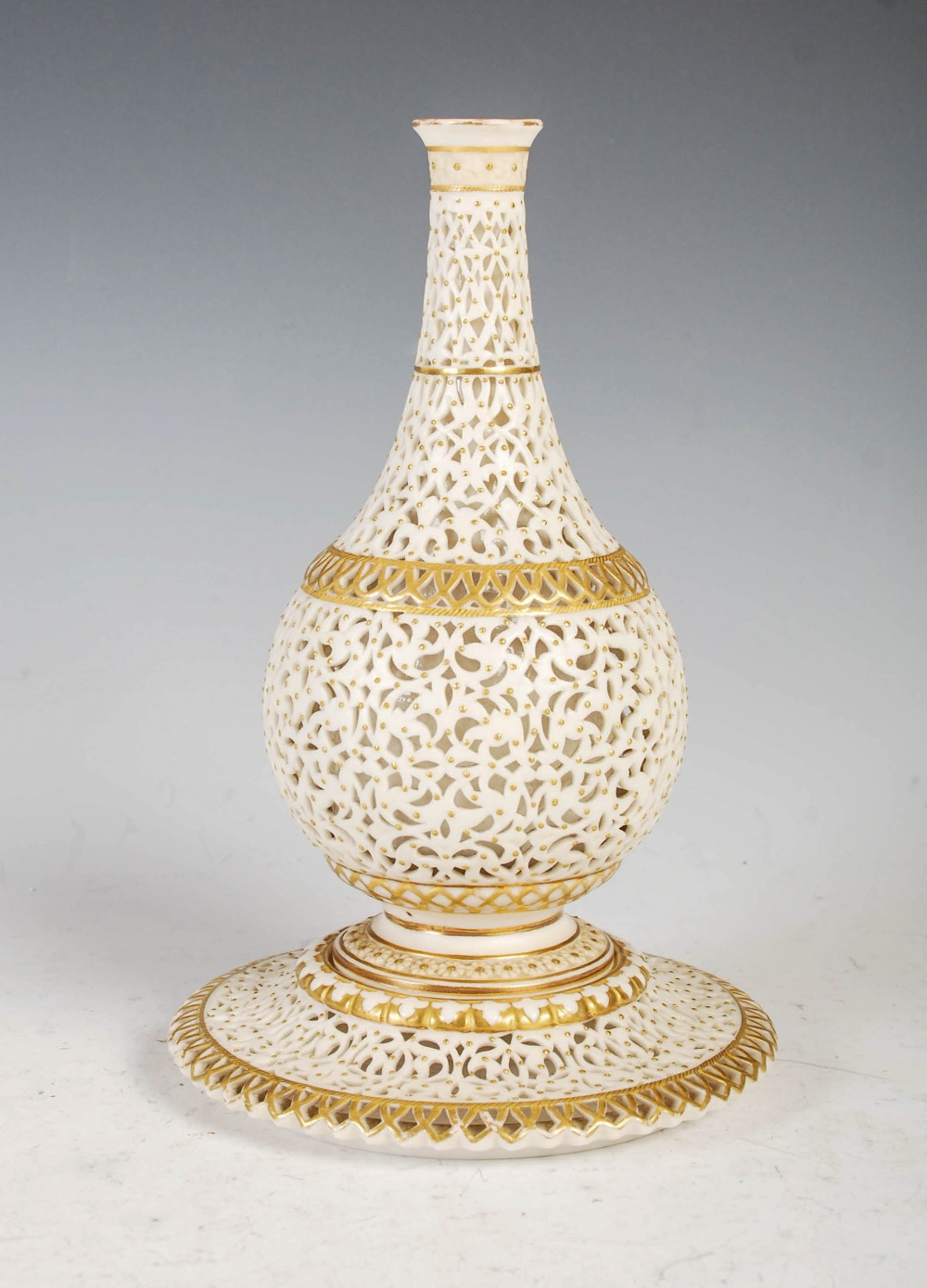 A Grainger & Co. Royal Worcester reticulated bottle vase, dated 1902, on integral circular stand,
