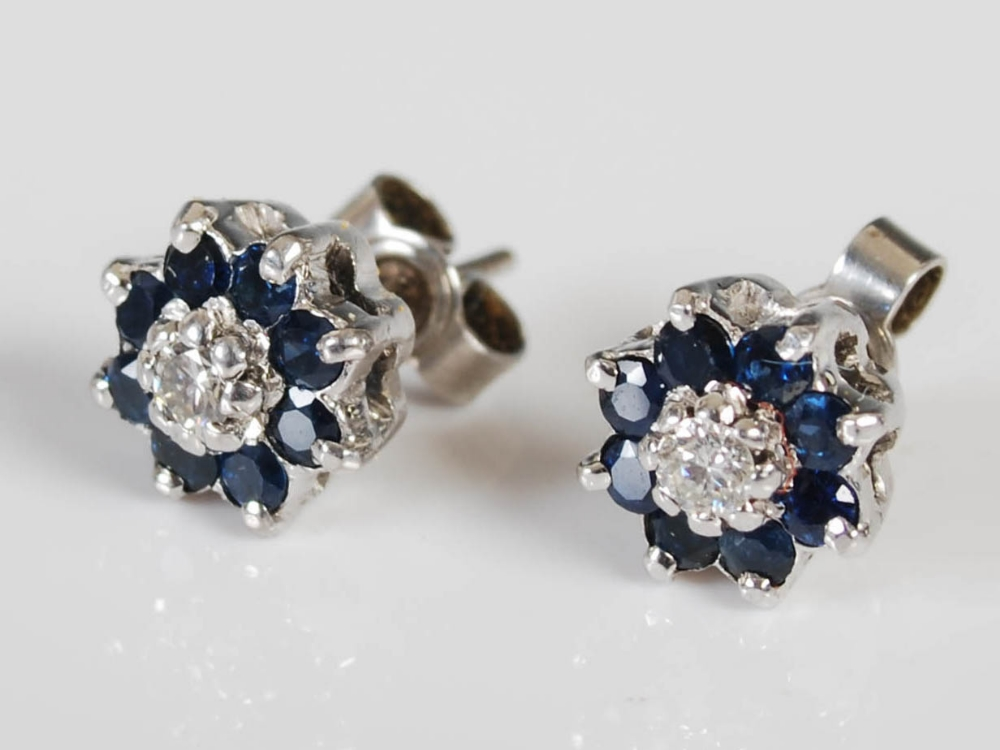 A pair of white metal sapphire and diamond set cluster earrings, circa 1970, each centred with a