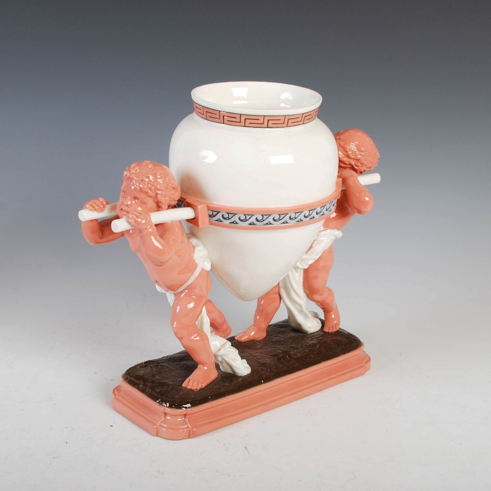 A Mintons table centrepiece, modelled in the form of two putti carrying a Grecian urn, impressed