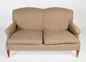 A two seat mahogany sofa in the style of Howard & Sons, the back, arms and loose cushion seat