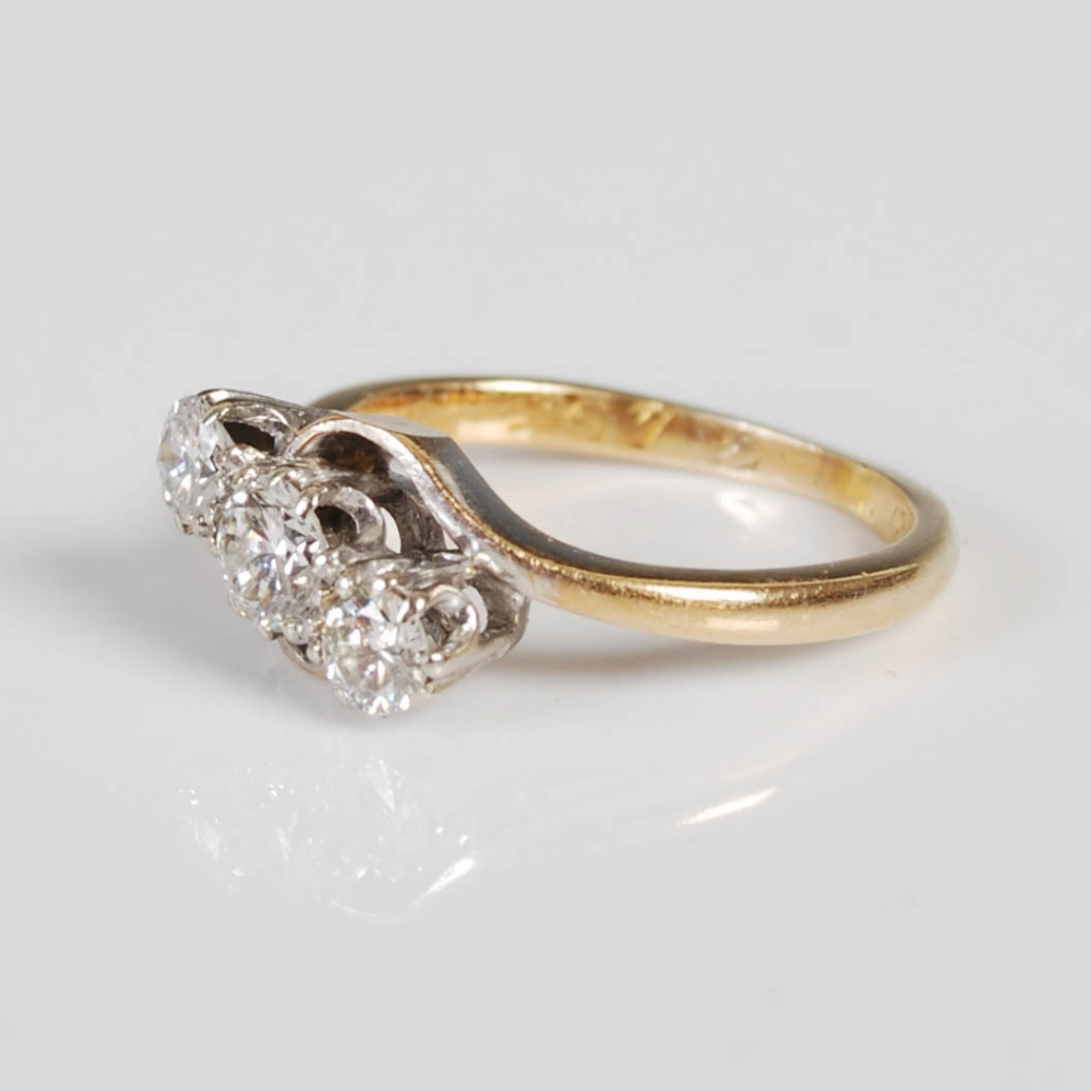 A yellow and white metal three stone diamond ring, mid 20th century, set with a single round - Image 2 of 6