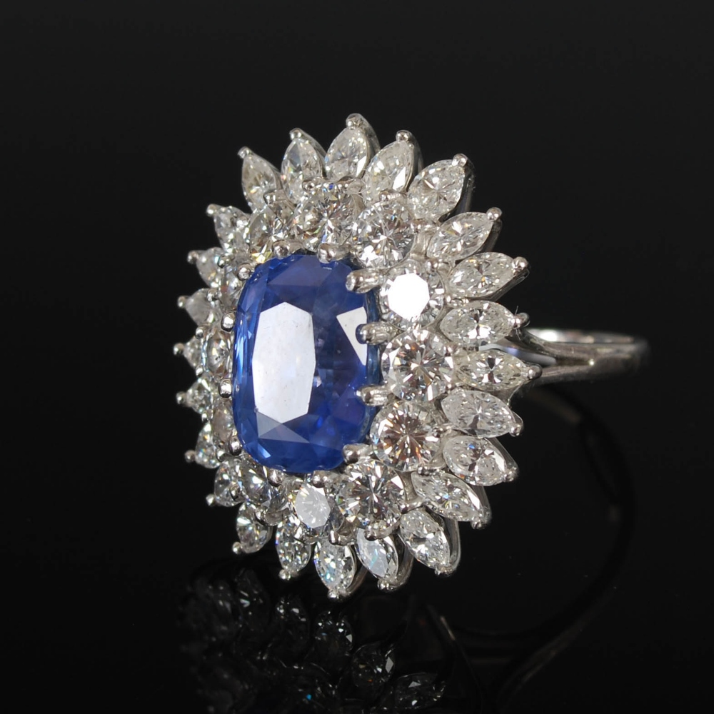 A white metal sapphire and diamond cluster ring, 20th century, centred with a rectangular cushion