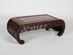 A Chinese dark wood Kang table, late Qing Dynasty, the rectangular panelled top above a pierced