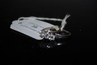A WHITE METAL THREE STONE DIAMOND RING, SET WITH THREE ROUND BRILLIANT CUT DIAMONDS WITH AVERAGE