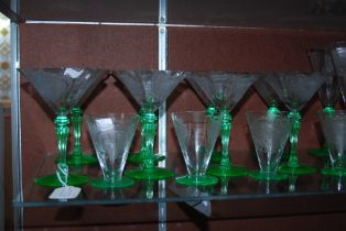 SUITE OF EARLY 20TH CENTURY ART DECO CLEAR AND GREEN GLASSWARE WITH ETCHED FIGURAL DECORATION.