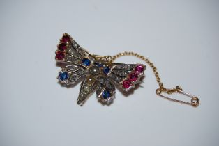 AN EARLY 20TH CENTURY YELLOW AND WHITE METAL SAPPHIRE, RUBY AND DIAMOND SET BUTTERFLY BROOCH
