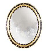An early 20th century ebonized and parcel gilt oval mirror,