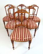 A set of six Edwardian walnut, amboyna, boxwood strung and marquetry dining chairs,