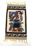A handwoven South American rug, the border surrounding a warrior in headdress,