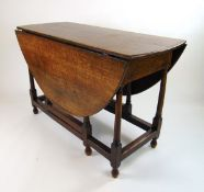 An 18th century oak drop leaf table, the oval top supported on a single gate action on turned legs,