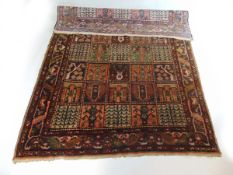 A handwoven Bakhtiari rug the triple line border surrounding the field with squares containing
