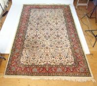 A handwoven Persian rug, the herati border surrounding a cream ground field with floral motifs,