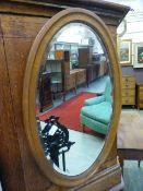An early 20th century oak bevel glass oval mirror