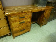 An Indonesian hardwood desk having a bank of three drawers with cupboard door