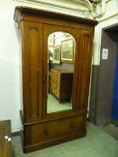 A Victorian mahogany veneered wardrobe having a mirrored bevelled glass centre door with drawer to