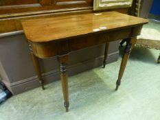 An early 19th century mahogany side table on turned legs,