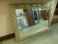 A silvered floral framed beveled glass rectangular mirror
