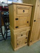 A pair of pine bedside cabinets having drawer over cupboard door