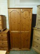 A modern pine two door wardrobe