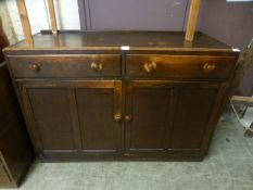 A mid 20th century oak sideboard with two drawers over two cupboard doors