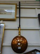 A brass and copper bed warming pan
