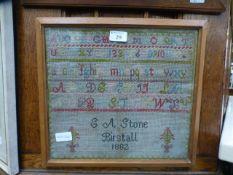 A framed and glazed sampler dated 1882