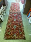 A pair of red ground rugs
