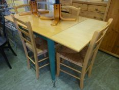 A modern beech extending kitchen table along with a set of four rush seated chairs