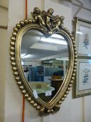 A gilt framed heart shaped mirror with cherubs to top