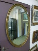 An oval gilt framed bevelled glass mirror