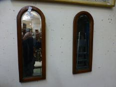 A pair of mahogany arch topped bevel glass mirrors