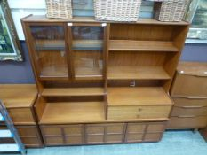 A mid-20th century teak cabinet having a part glazed top section with open storage,
