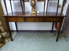 A reproduction mahogany three drawer serving table on square tapering supports