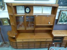 A mid-20th century teak unit having open storage above a pair of glazed doors and pull down front
