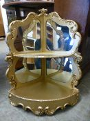 A gold painted and mirrored back multi level corner shelf
