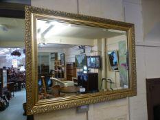 An ornate gilt framed bevelled glass mirror
