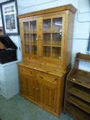 A modern pine dresser with glazed cupboard doors over drawers and cupboard doors