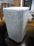 A cream painted wicker laundry basket