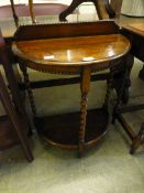 An early 20th century oak demi lune hall table
