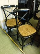 A pair of ebonised bentwood stools with cane seats